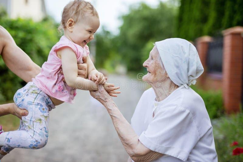 Menina feliz da criança e sua bisavó que olham um outro e riso foto de stock royalty free