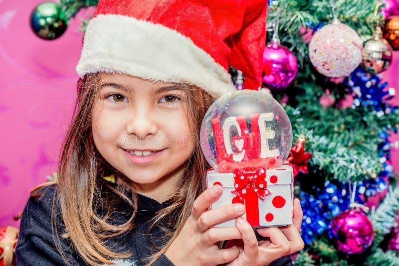 Menina feliz da criança em um chapéu do Natal que guarda o presente de vidro do globo de foto de stock