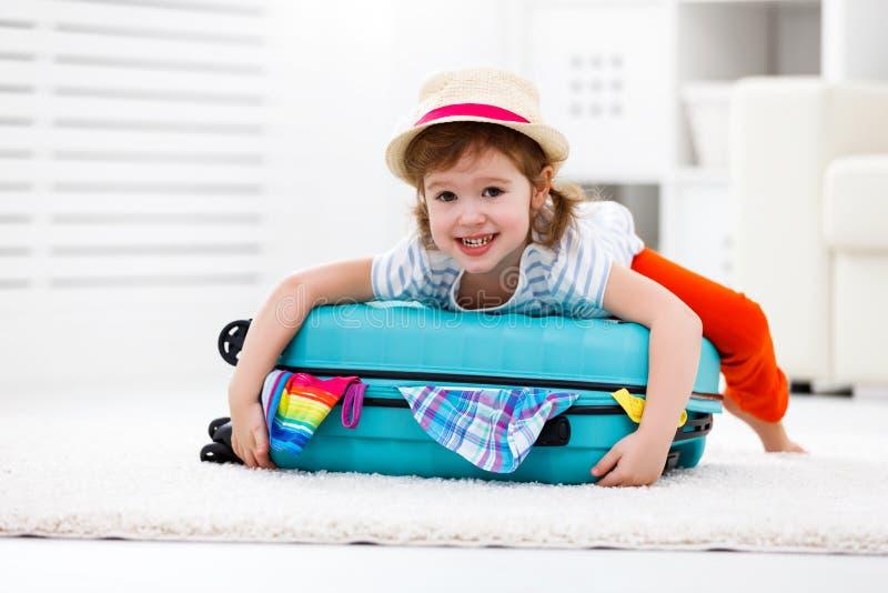 A menina feliz da criança embala a roupa na mala de viagem para o curso, vacatio imagens de stock