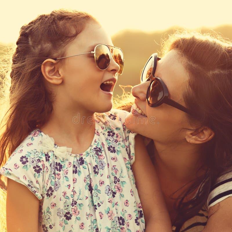 Menina feliz da criança da forma que fala a sua mãe em sunglass na moda imagens de stock royalty free