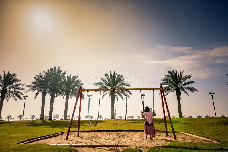 Menina feliz da criança no balanço no lago Dammam Arábia Saudita Modon da estação do inverno fotografia de stock