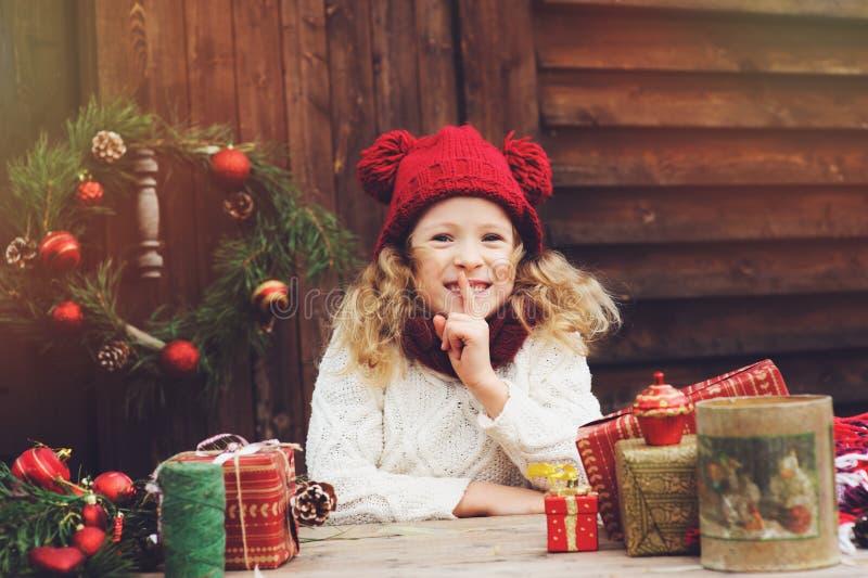 Menina feliz da criança no chapéu vermelho e no lenço que envolvem presentes do Natal na casa de campo acolhedor, decorada para o foto de stock royalty free