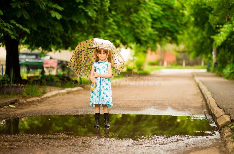 Menina feliz da criança no vestido com um guarda-chuva e umas botas de borracha na poça na caminhada imagens de stock royalty free