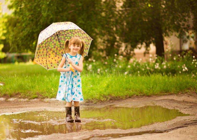 Menina feliz da criança no vestido com um guarda-chuva e umas botas de borracha na poça na caminhada fotografia de stock