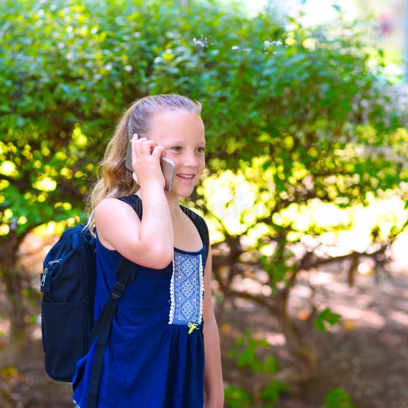 Menina feliz da criança pequena para ir educar e falando no telefone celular no parque da cidade foto de stock royalty free