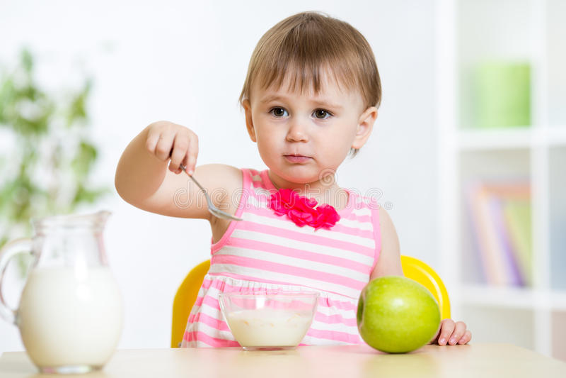 Menina feliz da criança que come o alimento próprio com colher imagem de stock