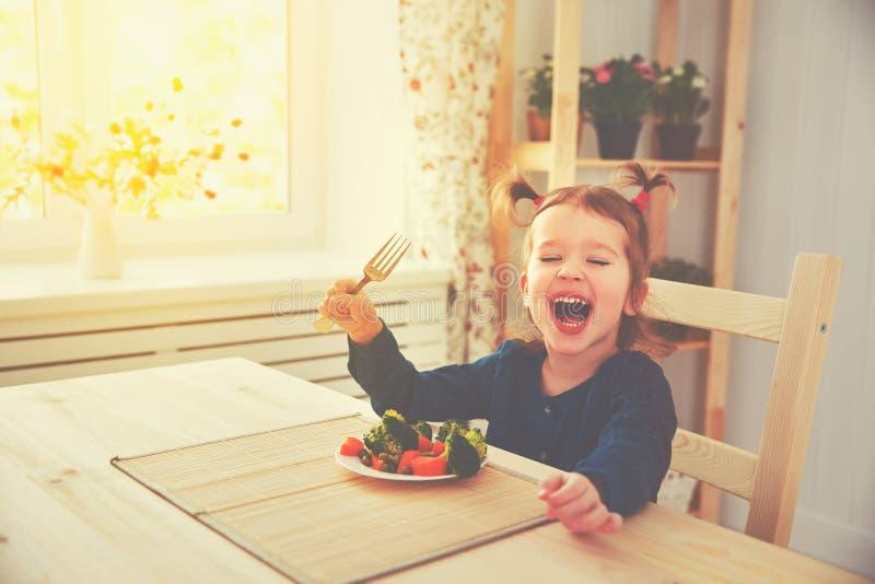 Menina feliz da criança que come vegetais e risos foto de stock