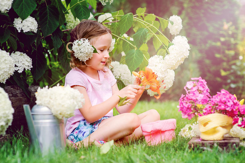 Menina feliz da criança que joga com as flores no jardim do verão no arbusto de florescência da hortênsia fotos de stock