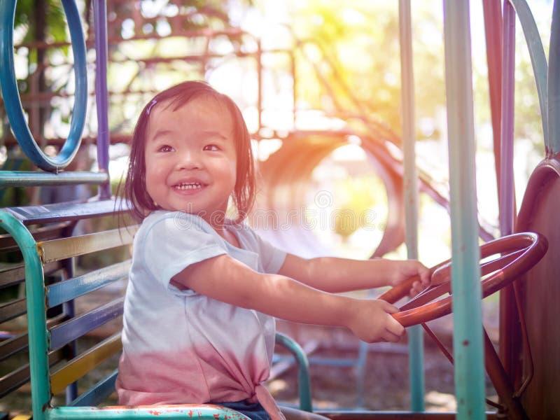 Menina feliz da criança que joga no carrossel no parque em um dia muito ensolarado Crianças adoráveis que passam o tempo feliz foto de stock royalty free