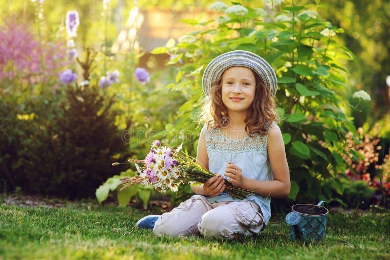 Menina feliz da criança que joga o jardineiro pequeno no verão, no chapéu engraçado vestindo e guardando o ramalhete das flores fotografia de stock