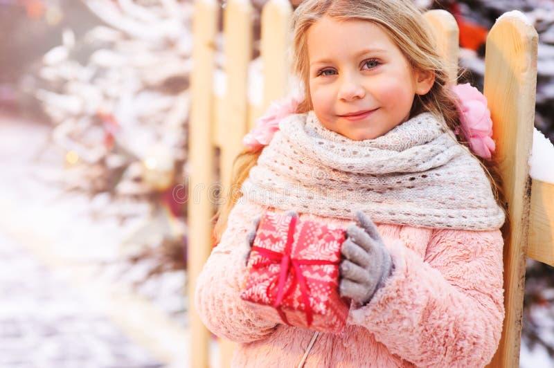 menina feliz da criança que mantém o presente do Natal exterior na caminhada na cidade nevado do inverno decorada pelo ano novo foto de stock