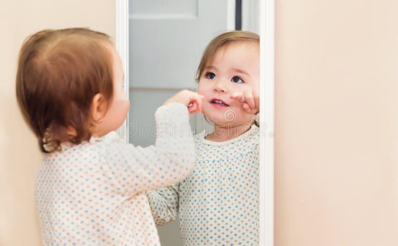 Menina feliz da criança que olha si mesma no espelho imagens de stock