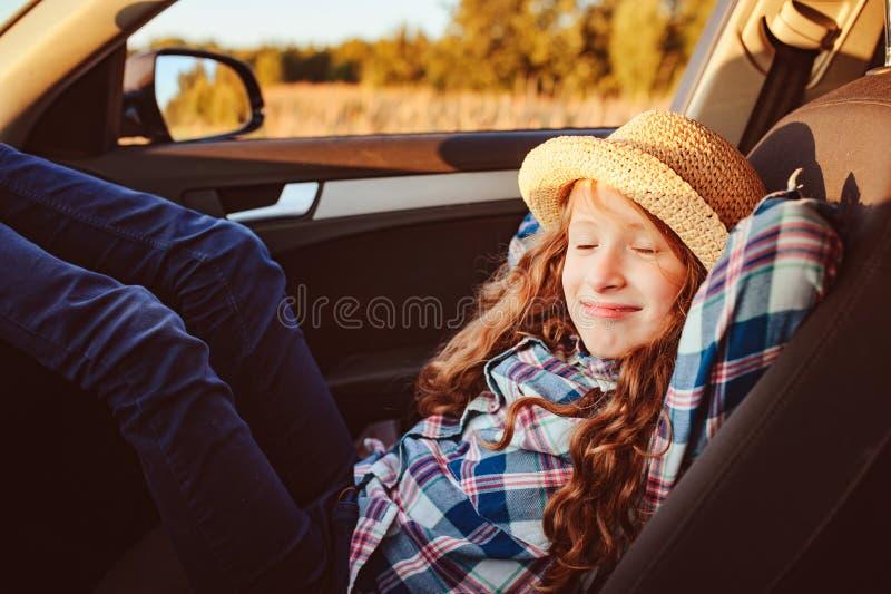 Menina feliz da criança que relaxa no carro durante a viagem por estrada do verão fotos de stock royalty free