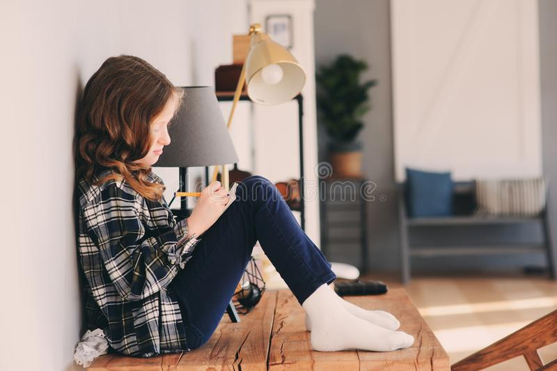 a menina feliz da criança que senta-se na tabela em casa e torce-se imagem de stock royalty free
