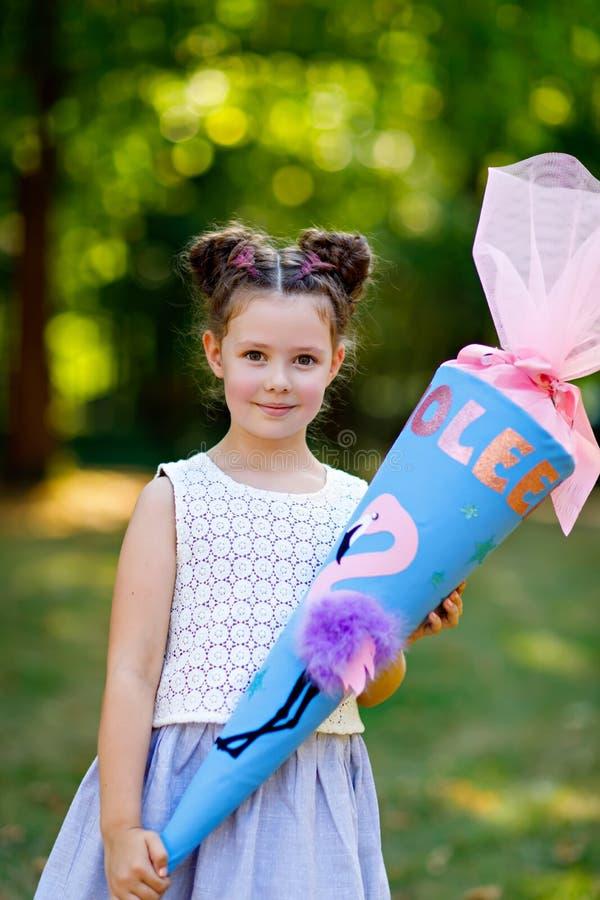 Menina feliz da crian?a com trouxa ou sacola e saco de escola grande ou cone tradicional em Alemanha para o primeiro dia de imagens de stock