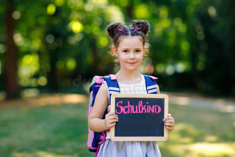 Menina feliz da crian?a que est? com mesa e trouxa ou sacola Aluno no primeiro dia da classe elementar Saud?vel foto de stock royalty free