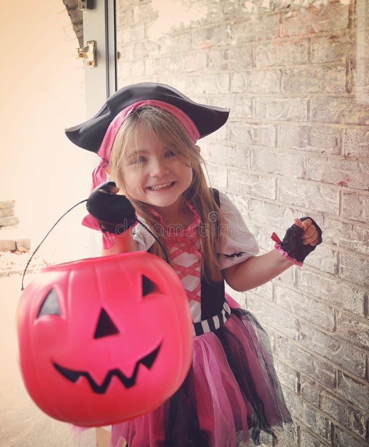 Menina feliz da doçura ou travessura de Dia das Bruxas na porta imagens de stock