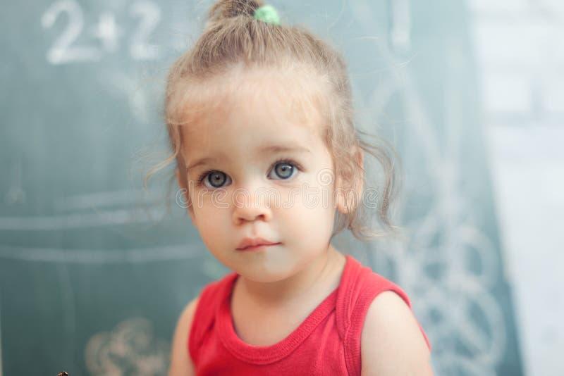 A menina feliz da escola na matemática classifica no jardim de infância que encontra a solução e que resolve problemas fotografia de stock royalty free