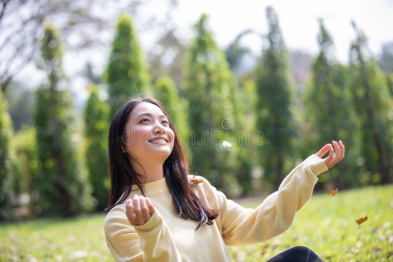 Menina feliz de sorriso da mulher asi?tica bonita e roupa morna vestindo inverno e retrato do outono em exterior no parque foto de stock royalty free