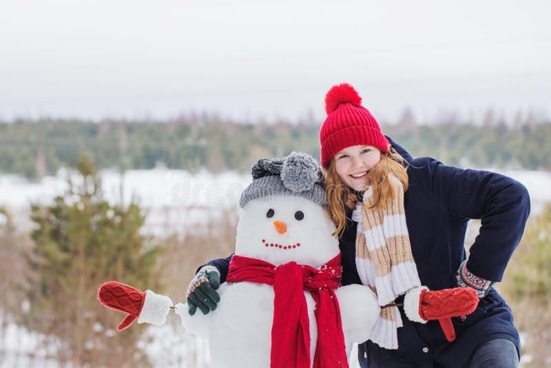 Menina feliz do adolescente com boneco de neve fotos de stock