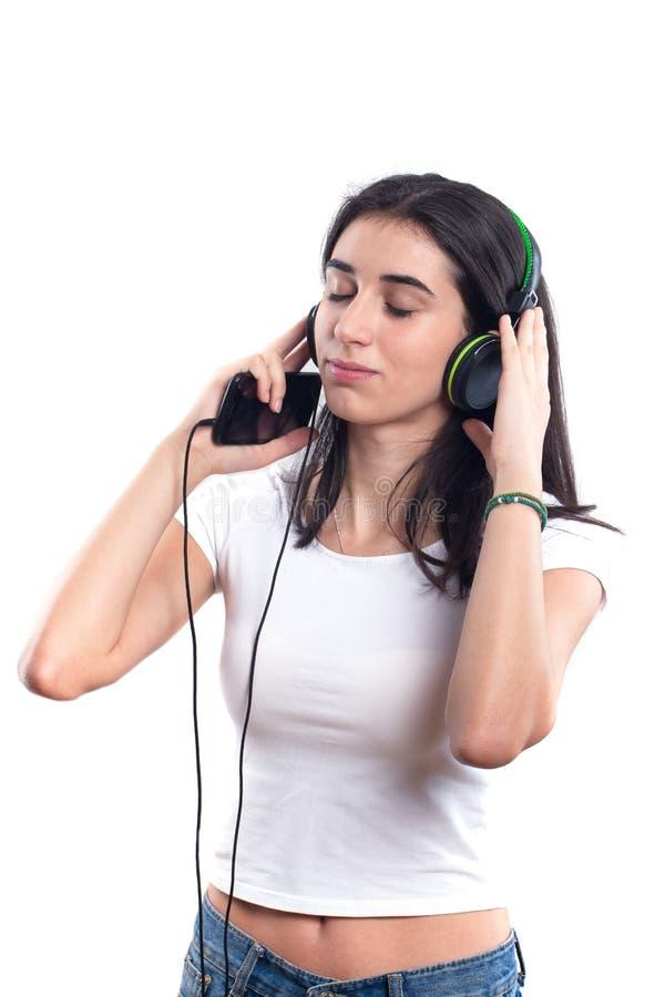Menina feliz do adolescente que escuta a música isolada em um b branco imagens de stock royalty free