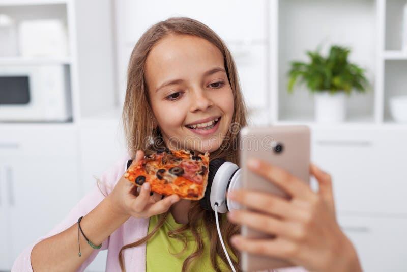 Menina feliz do adolescente que toma um selfie na cozinha que levanta com uma fatia de pizza fotografia de stock royalty free