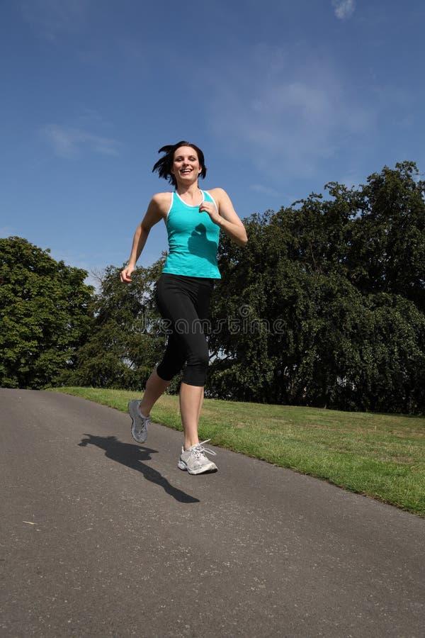 Menina feliz do atleta que funciona na velocidade no parque fotografia de stock royalty free