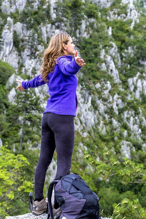 Menina feliz do caminhante que comemora na parte superior da montanha com braços acima imagem de stock royalty free