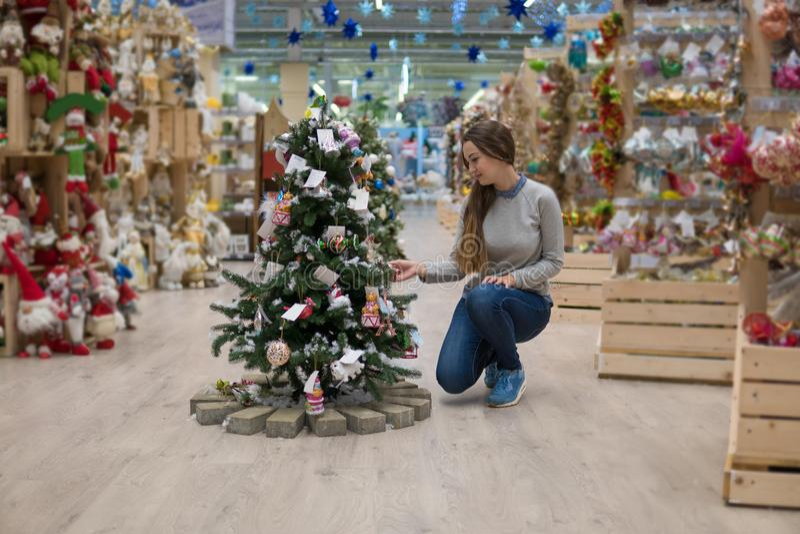 Menina feliz do cliente que escolhe a árvore de Natal pelo ano novo fotografia de stock royalty free