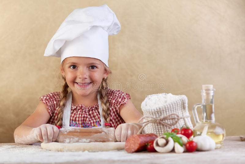 Menina feliz do cozinheiro chefe que estica a massa imagens de stock