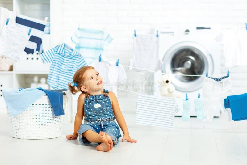 Menina feliz do divertimento da criança para lavar a roupa e os risos no laund imagens de stock