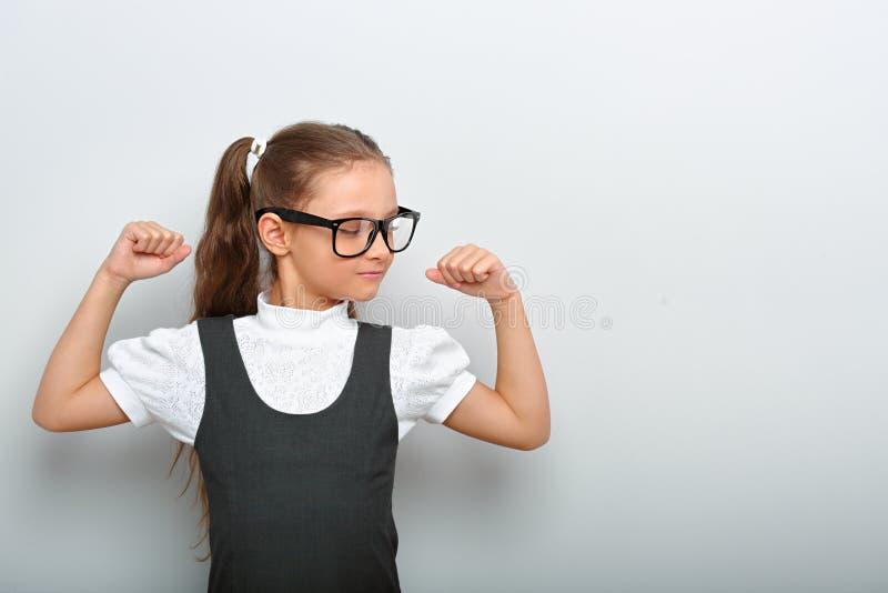 Menina feliz do divertimento nos monóculos que mostram seus braços do músculo na escola u imagem de stock royalty free