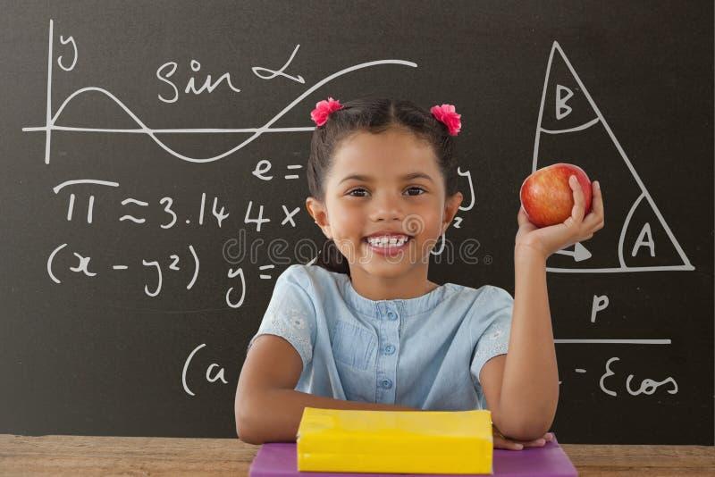 Menina feliz do estudante na tabela que mantém uma maçã contra o quadro-negro cinzento com educação e gráfico da escola fotos de stock royalty free