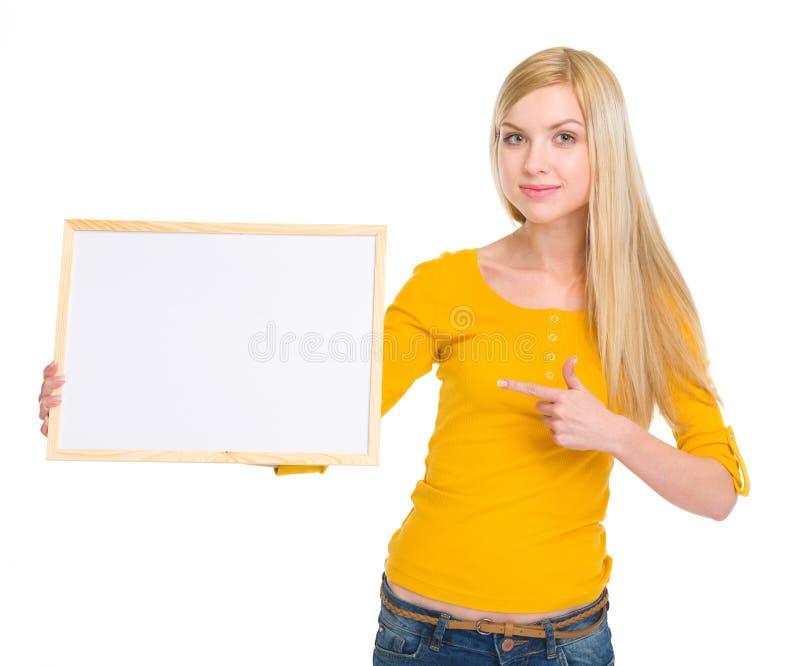 Menina feliz do estudante que aponta na placa vazia fotografia de stock