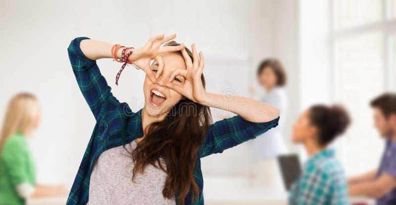 Menina feliz do estudante que faz a cara na escola foto de stock