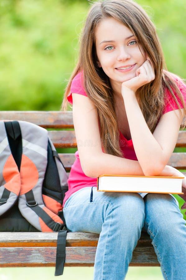 Menina feliz do estudante que senta-se no banco com livro fotos de stock royalty free