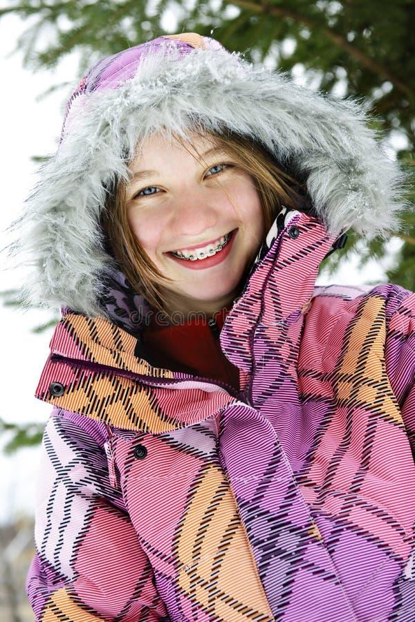 Menina feliz do inverno no revestimento de esqui foto de stock royalty free