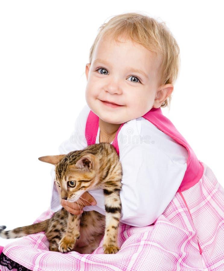 Menina feliz do ittle que abraça o gatinho Isolado no fundo branco fotos de stock royalty free