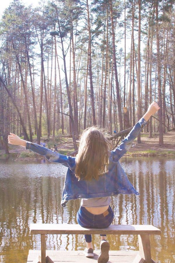 Menina feliz do jovem adolescente perto do lago da floresta imagens de stock royalty free
