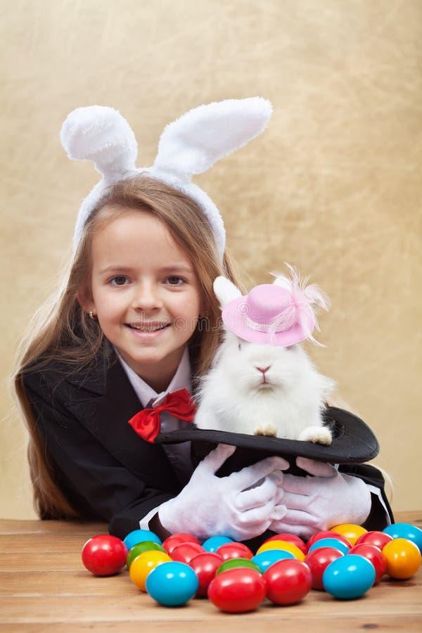 Menina feliz do mágico que guarda o coelho bonito no chapéu mágico imagens de stock