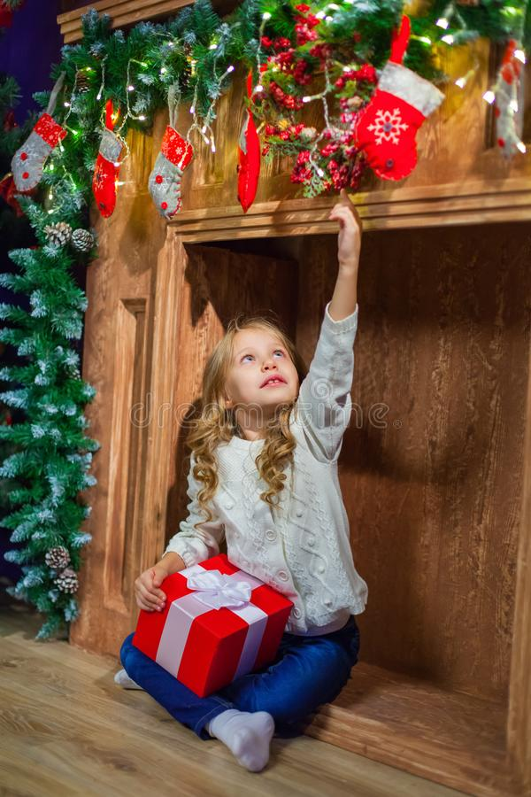 Menina feliz do Feliz Natal com presente mágico em casa perto de Christma foto de stock