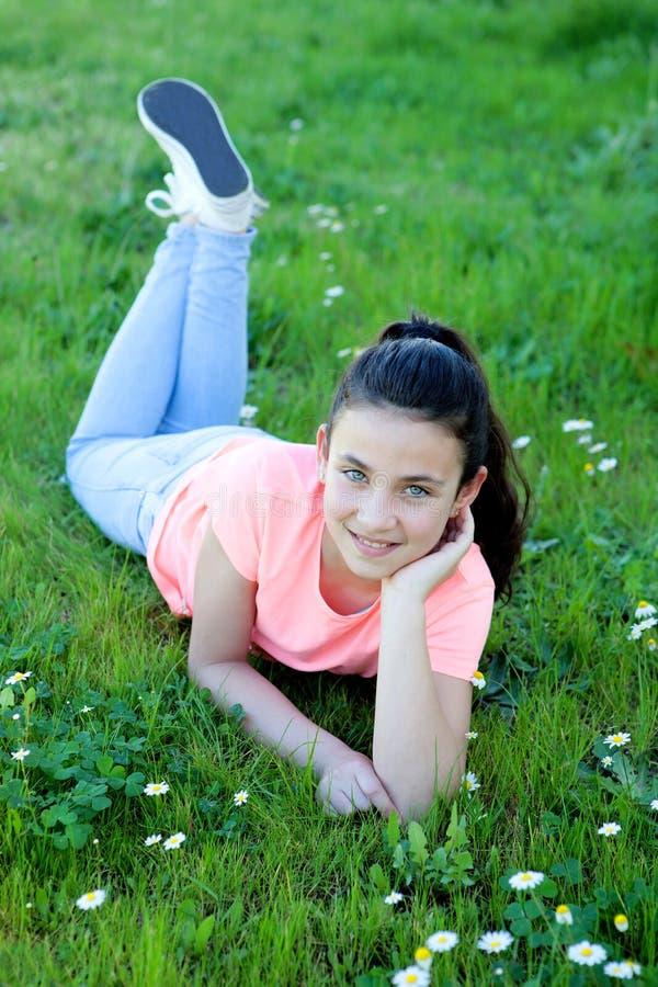 Menina feliz do preteen que encontra-se na grama foto de stock royalty free
