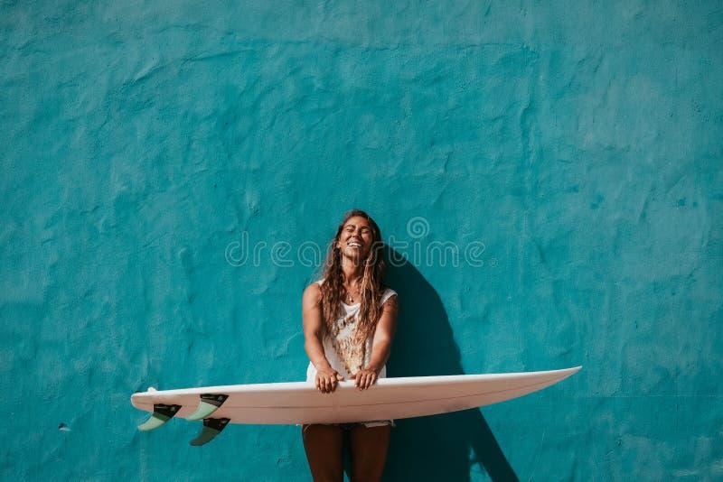 Menina feliz do surfista com a prancha na frente da parede azul foto de stock