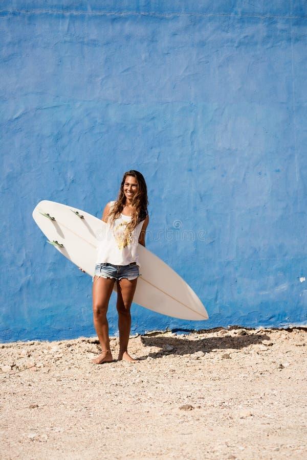Menina feliz do surfista com a prancha na frente da parede azul imagem de stock royalty free