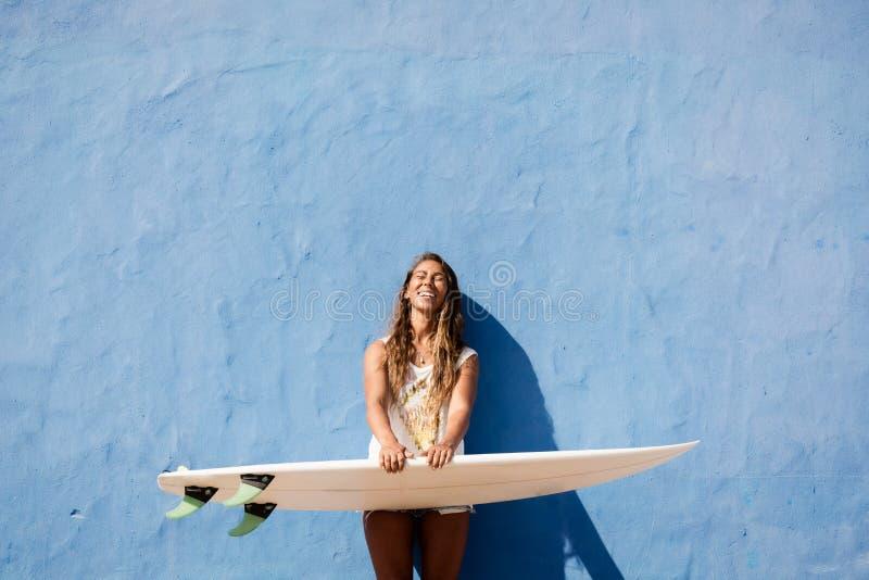 Menina feliz do surfista com a prancha na frente da parede azul imagens de stock