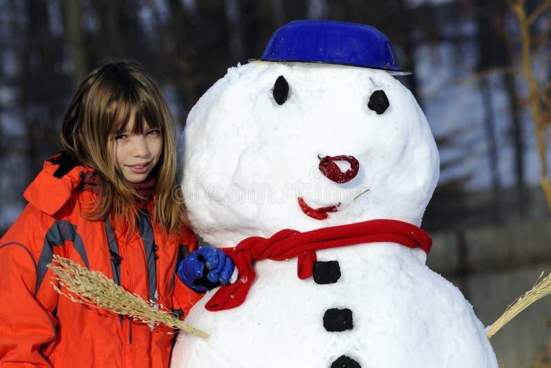 Menina feliz e boneco de neve engraçado imagens de stock