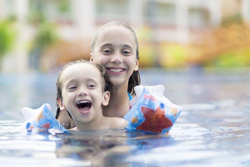 Menina feliz e menino que apreciam na piscina fotografia de stock royalty free