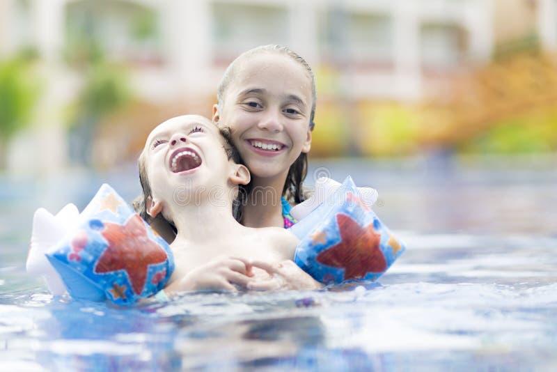 Menina feliz e menino que apreciam na piscina fotografia de stock