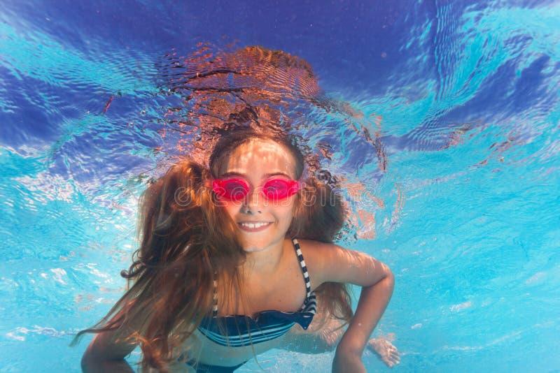 Menina feliz em óculos de proteção cor-de-rosa que nada sob a água imagem de stock royalty free