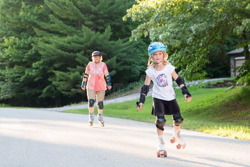 Menina feliz em patins com a mulher no fundo fotografia de stock